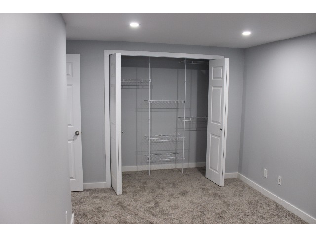 Large master bedroom with his and hers closet organizer. Plenty of room for a queen bed plus bedroom set