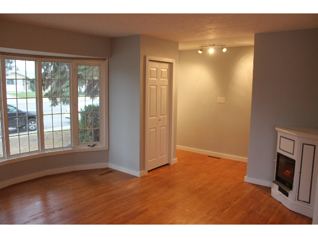 Entrance into hallway and large living room with front hall coat closet and corner electric fireplace. Wired for TV above fireplace.