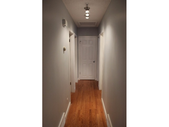 Hallway off kitchen leading to 3 bedrooms, bathroom, and hall linen closet at end.